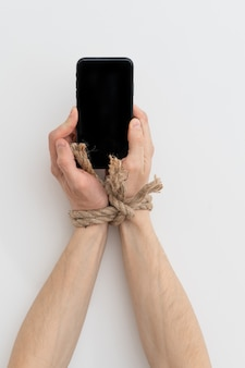ロープで結ばれたインターネット中毒またはソーシャルメディア中毒の手はスマートフォンを保持します