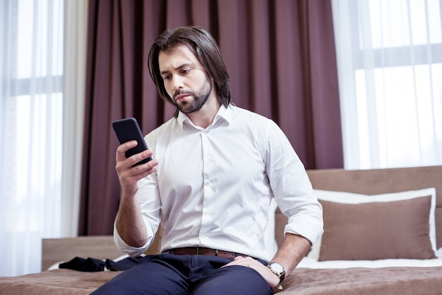 Internet age. serious good looking man using his smartphone while checking his social media