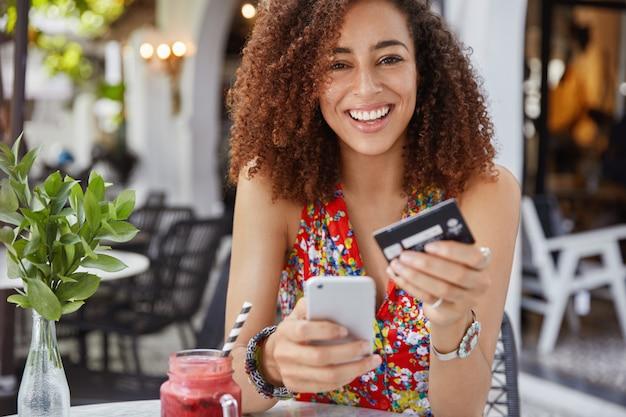 インターネットバンキングとeコマースのコンセプトです。アフロの髪型と幸せな若い笑顔の女性は、オンラインショッピングに現代の携帯電話とクレジットカードを使用しています