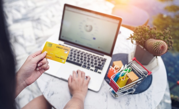 Internet banking and online shopping concepts, woman hands holding using credit card for money transfering