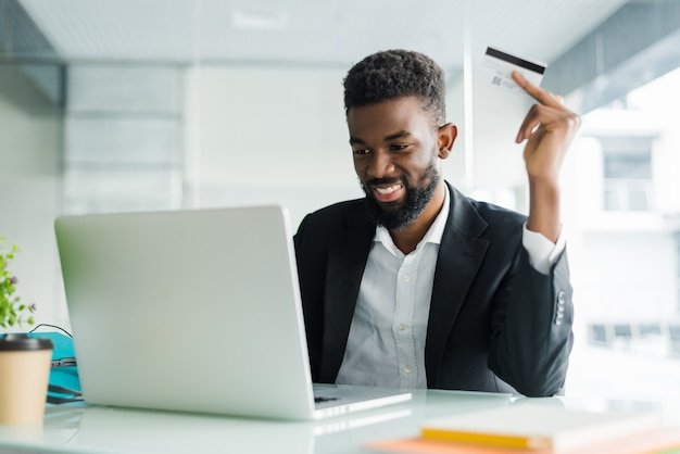 Internet banking sales. successful african businessman sitting at a laptop and holding credit card in hand until businessman doing orders through the internet