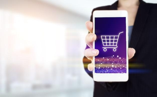 インターネットカートウェブストアオンライン購入eコマースの概念。明るいぼやけた背景にデジタルホログラムカートサインと白いスマートフォンを手に持ってください。オンラインショッピングビジネス技術インターネットの概念。