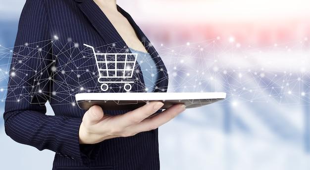 인터넷 장바구니 웹 스토어 온라인 전자 상거래 개념을 구매합니다. 밝은 배경에 디지털 홀로그램 카트 표시가 있는 흰색 태블릿을 손에 들고 있습니다. 온라인 쇼핑, 온라인 상점 응용 프로그램입니다.