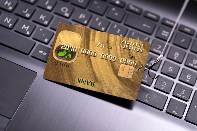 컴퓨터 기술을 사용한 인터넷 사기, 인터넷에서 돈을 훔치는 것, 신용 카드 데이터를 훔치는 것. 노트북 키보드 배경에 후크 후크 신용 카드.