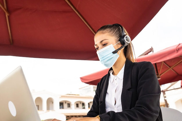 Internet freelance job choice concept: a young cute woman with wireless headphones works on her laptop wearing a medical mask on a table of a bar - new normal jobs with remote connections and covid 19
