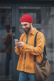 On internet. man in an orange jacket with a phone in his hands