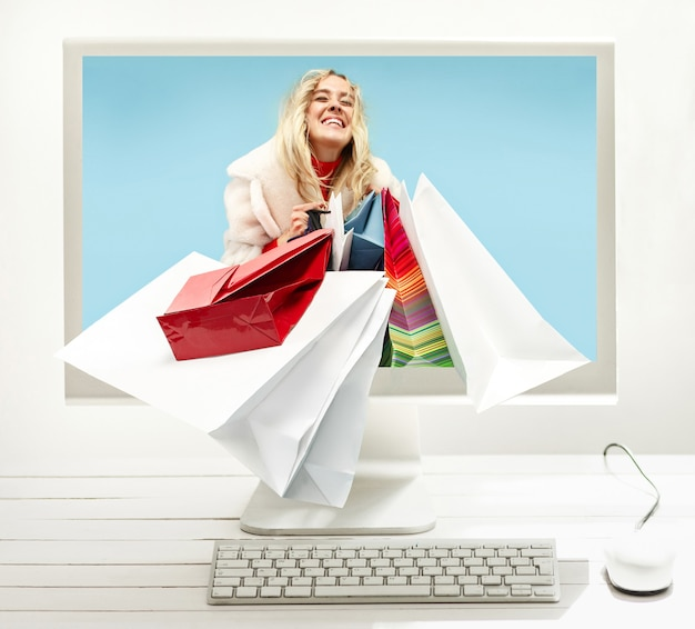 Internet online shopping concept with computer and cart. collage with stylish white workspace with computer on home or studio