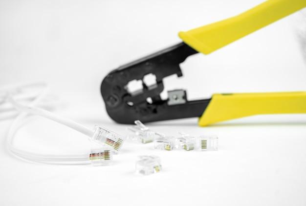 インターネットまたは電話回線ケーブルとクリンパは白い背景で隔離されています