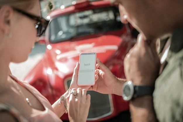 인터넷 검색. 스마트폰을 함께 들고 있는 집중된 부부는 새 차에 대한 정보를 찾고 있습니다.