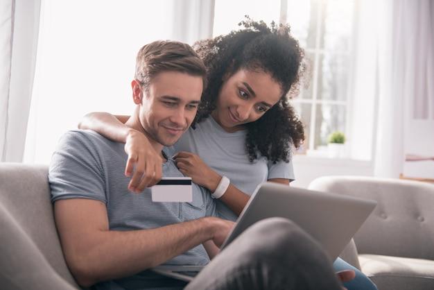 インターネットショッピング。ノートパソコンの画面を見ながら一緒に座って幸せな素敵なカップル