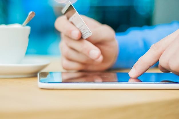인터넷 쇼핑 남자 온라인 태블릿 pc와 신용 카드. 인터넷에서 물건을 사는 인터넷 쇼핑객.