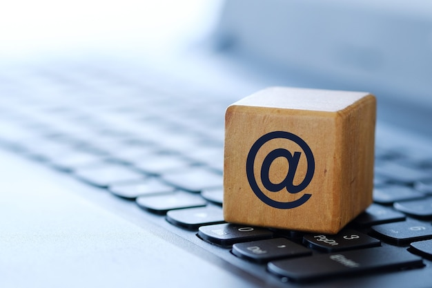 ぼやけた背景と浅い被写界深度を持つ、コンピューターのキーボード上の木製の立方体のインターネットシンボル。