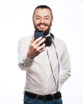 インターネット、技術、人々の概念。携帯電話を持って白の上に立って自分の写真を撮るシャツのひげを生やした若い男