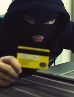 Интернет-кража - мужчина в балаклаве, держащий кредитную карту, сидел за ноутбуком, белый фон.