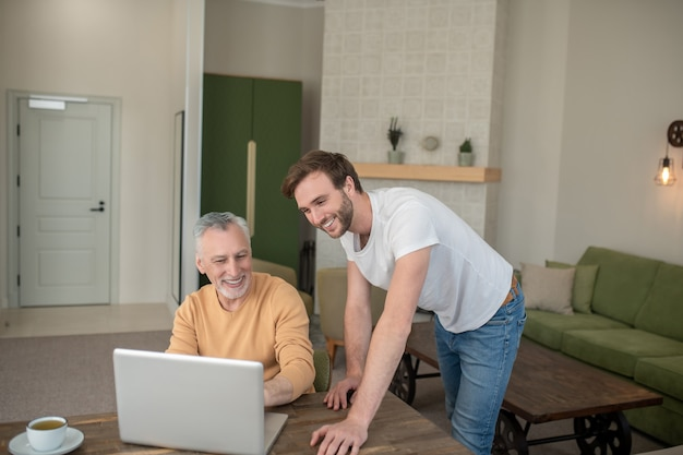 On internet. two men in the room at the laptop watching something on a laptop