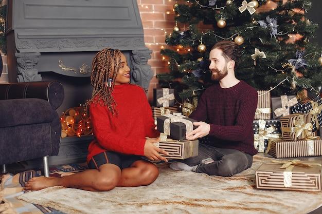自宅のインターネットの人々。クリスマスの飾りのカップル。アフリカの女性と白人の男性。