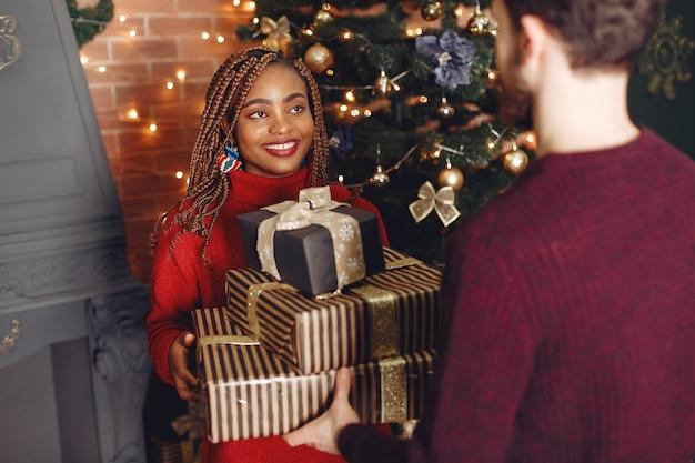 Дома интернета. пара в рождественских украшениях. африканская женщина и кавказский мужчина.