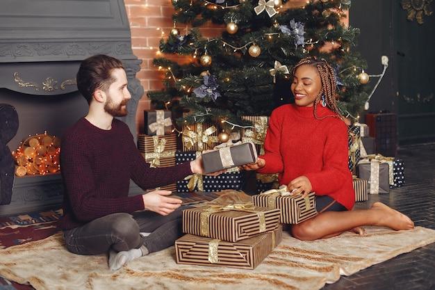 Persone internazionali a casa. coppia in una decorazioni natalizie. donna africana e uomo caucasico.