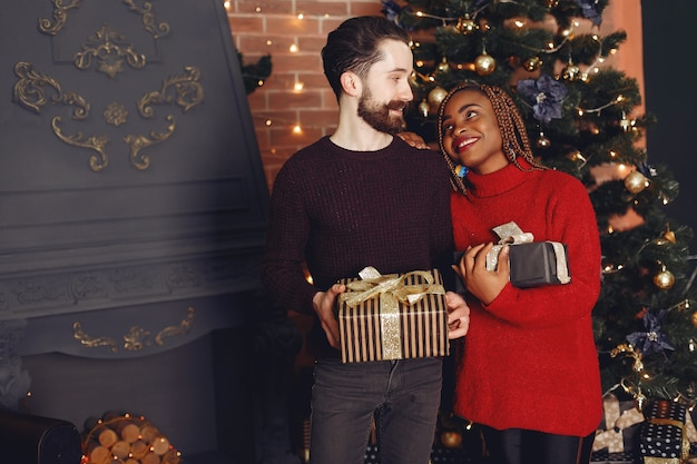Internetional people at home. couple in a christmas decorations. african woman and caucasian man.