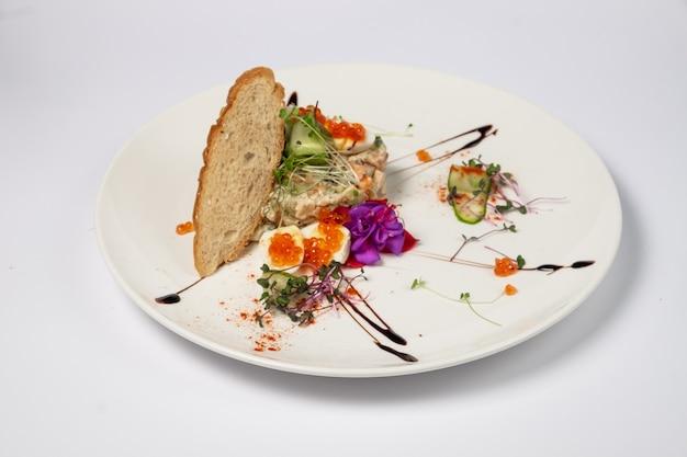 Интерпретация салата оливье с жареным куриным филе, перепелиными яйцами и красной икрой на белой поверхности.