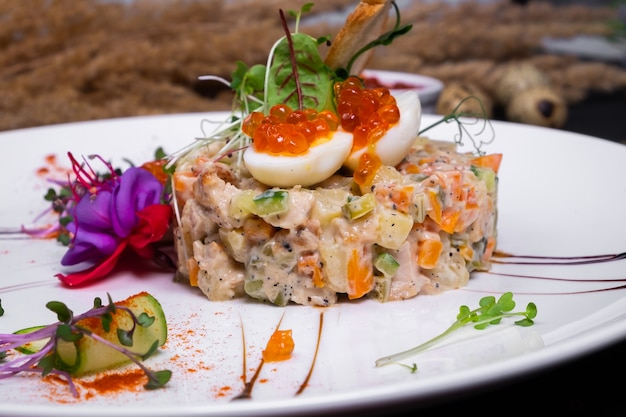 Interpretation of olivier salad with grilled chicken fillet, quail eggs and red caviar, on a dark surface. close up view