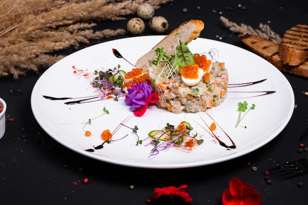 Interpretation of olivier salad with grilled chicken fillet, quail eggs and red caviar, on a dark surface.
