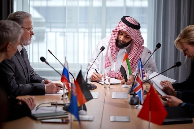 Межрасовые бизнес-субъекты, собравшиеся вместе для переговорной встречи под руководством арабского бизнесмена, обсуждения, выражения мнения, предложения решений, решения текущих вопросов, концепции партнерства
