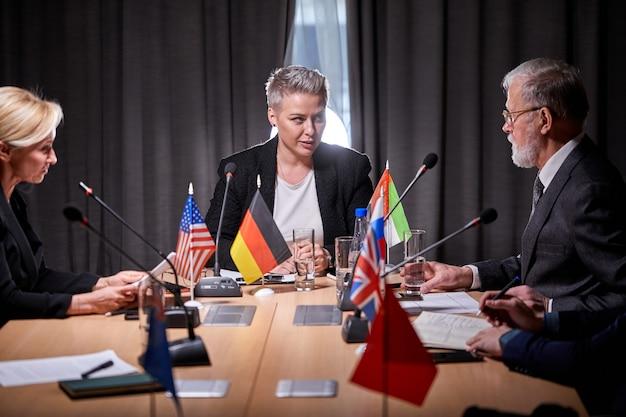 Межрасовые бизнес-субъекты, собравшиеся вместе для переговоров, под руководством кавказской бизнес-леди, обсуждения, выражения мнения, предложения решений, решения текущих вопросов, концепции партнерства