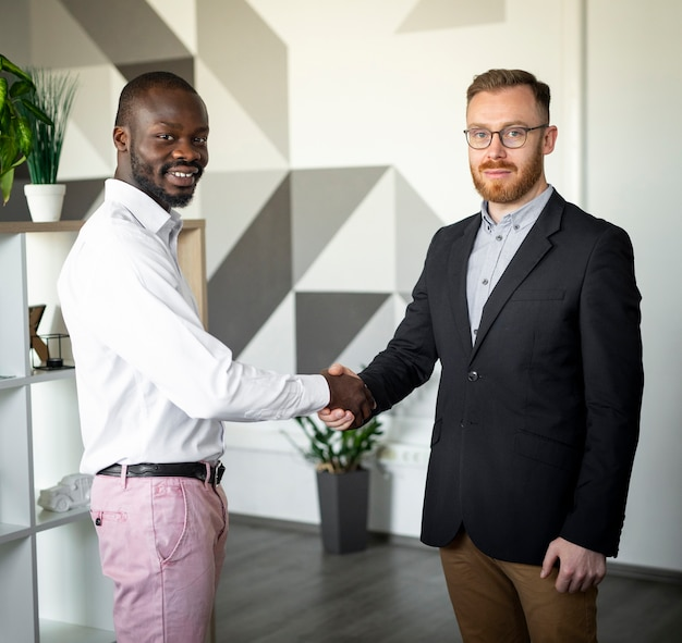 Interracial colleagues shaking hands