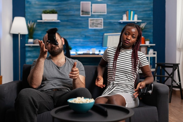 Межрасовая пара грустит после проигрыша в видеоигре. многонациональные партнеры играют с контроллерами и консолями по телевизору. люди смешанной расы с веселой игрой и джойстиками