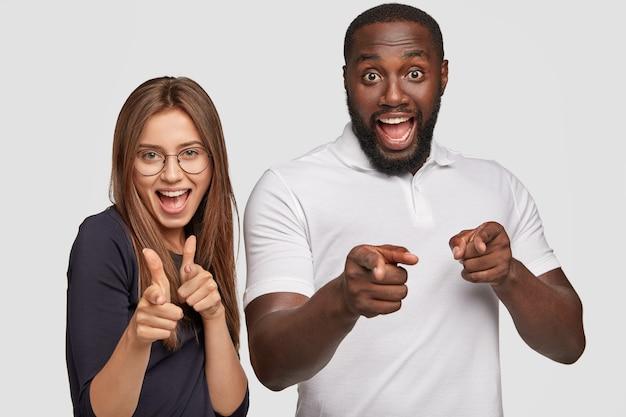 Межрасовая пара имеет позитивное выражение лица, уверенно смотрит на вас, смотрит вдаль