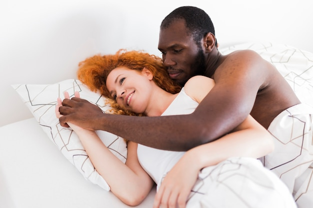 Interracial couple holding hands in bed