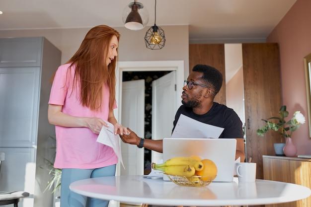 メールを読んで、自宅のキッチンで会計をチェックする異人種間のカップル
