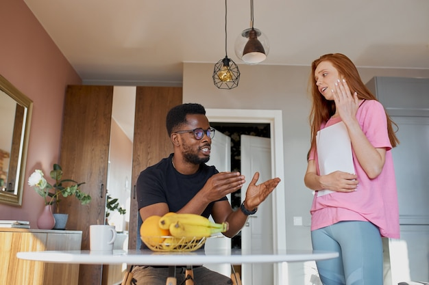Interracial couple reading mail and checking accounting in the kitchen at home