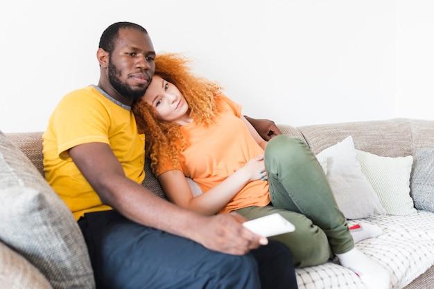 Interracial couple resting on a sofa