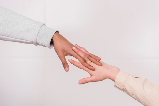 Interracial couple's hand against white background