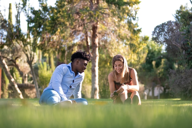 Interracial couple seated on the grass of a park. using their mobile phones.