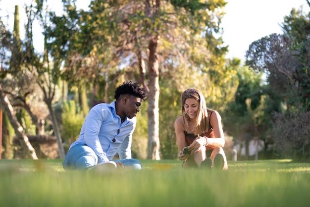 공원의 잔디에 앉아 인종 커플. 휴대전화 사용.