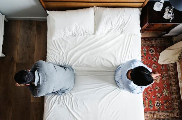 침대에 연달아 앉아있는 인종 커플