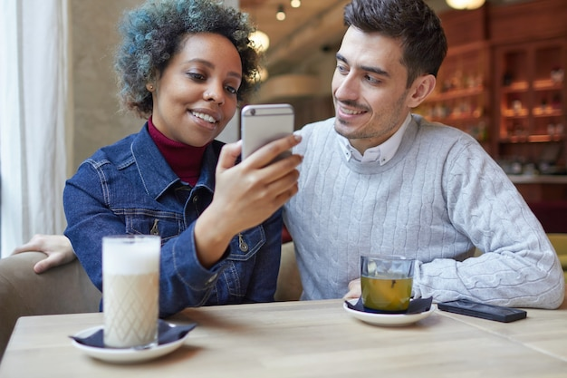 Interracial couple sitting in cafe and sharing new video using smartphone