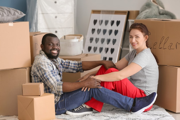 Interracial couple sitting on floor near boxes. moving into new house