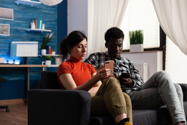 ガジェットでリラックスしてソファに座っている異人種間のカップル。テクノロジーを搭載したスマートフォンを使用している白人女性とアフリカ系アメリカ人男性。電話デバイスを保持している混血パートナー。
