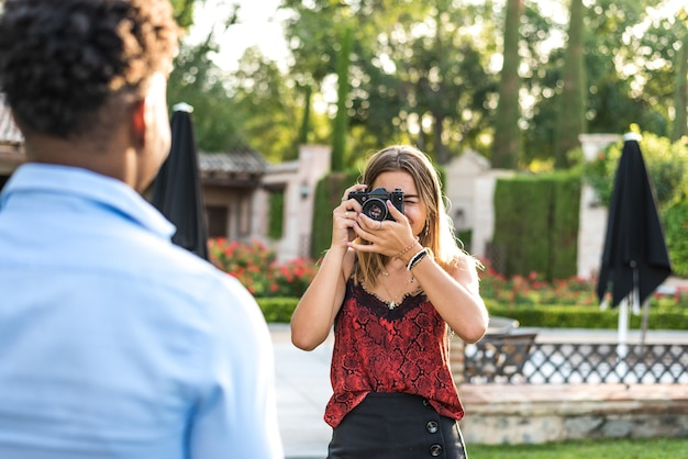 Interracial couple taking pictures with a vintage camera. caucasian woman taking pictures of black guy.