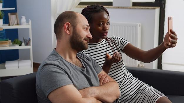 Межрасовая пара разговаривает и машет на видеоконференции