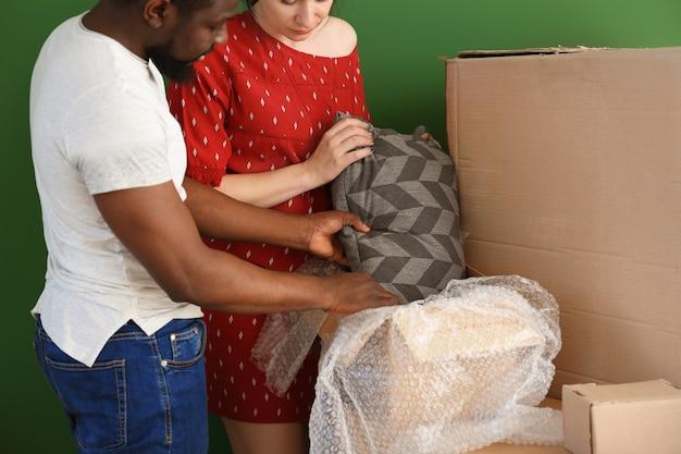 Межрасовая пара распаковывает коробку в помещении. переезд в новый дом