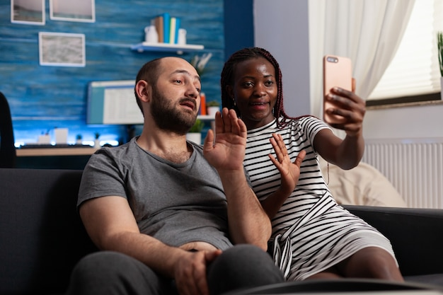 Interracial couple waving at camera while using video call communication. multi ethnic people holding modern smartphone with online remote conference on internet connection at home.
