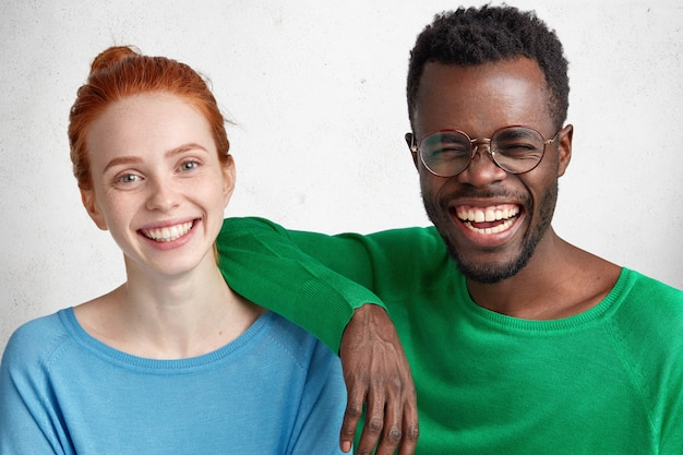 Interracial female and male friends have fun together: overjoyed dark skinned male laughs at good joke