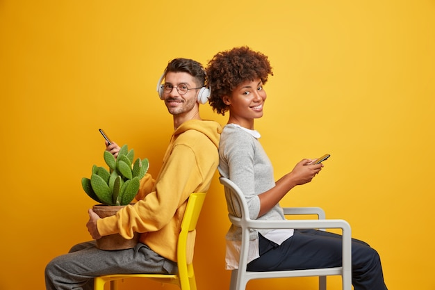 Interracial friends pose on chairs against vivid yellow wall, hold mobile phones and look with cheerful expressions