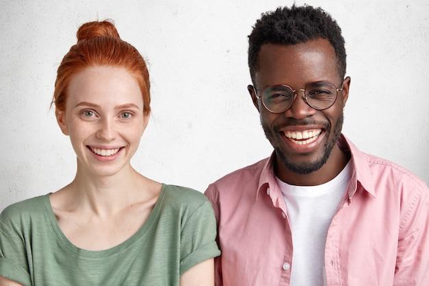 異人種間の友情の概念。健康な肌と黒い肌の大喜びの男性のそばかすのある美しい女性が眼鏡をかけています