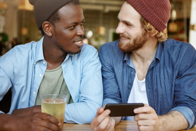 Interracial friendship concept. two cheerful attractive young men of different races having alcoholic drinks at bar: white male holding smart phone, showing something to his dark-skinned friend